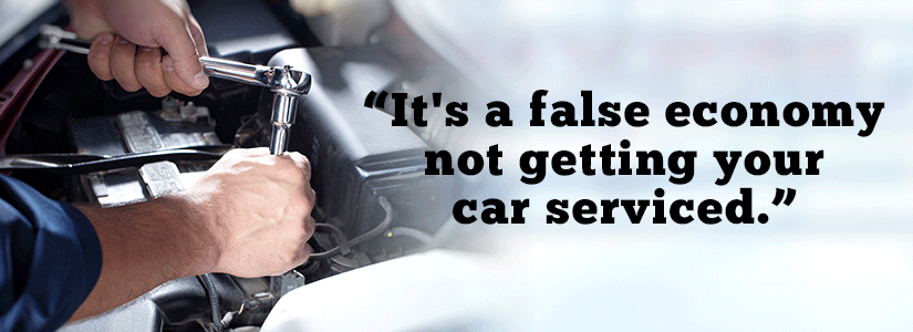 An image of a mechanic servicing a car with the caption it's a false economy not getting your car serviced