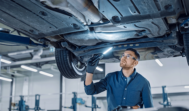 Mechanic inspecting the underneath of a car